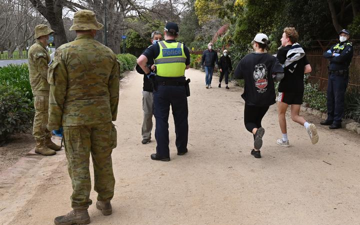 Police and soldiers patrol a running track while people exercise in Melbourne on 7 August 2020, as the city goes into a strict new lockdown after an outbreak of the Covid-19 coronavirus.