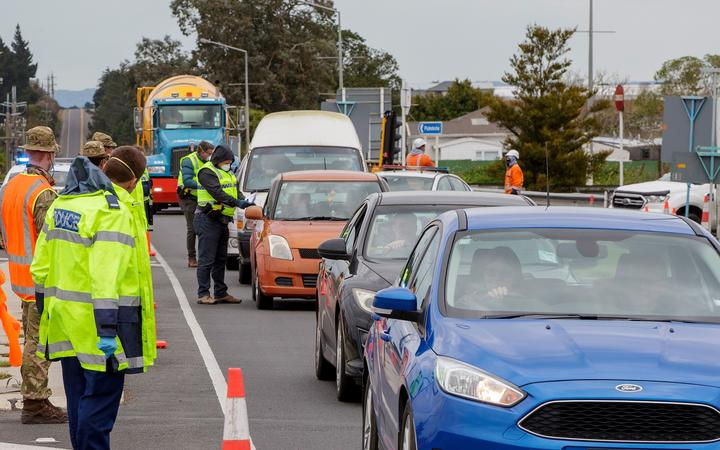 Police and military personnel check vehicles leaving the city at a COVID-19 check point setup at the southern boundary in Auckland on August 14, 2020.
