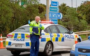 A police officer directs a driver wanting to leave the city at a COVID-19 check point setup at the southern boundary in Auckland on August 14, 2020.