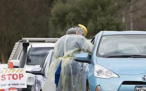 A health worker conducts a COVID-19 test in a drive through Community Based Assessment Centre in Christchurch, New Zealand, on August 14, 2020.