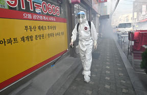 A health official wearing protective gear sprays disinfectant on the street near the Sarang Jeil Church, a new coronavirus infection cluster, in South Korea's capital Seoul.