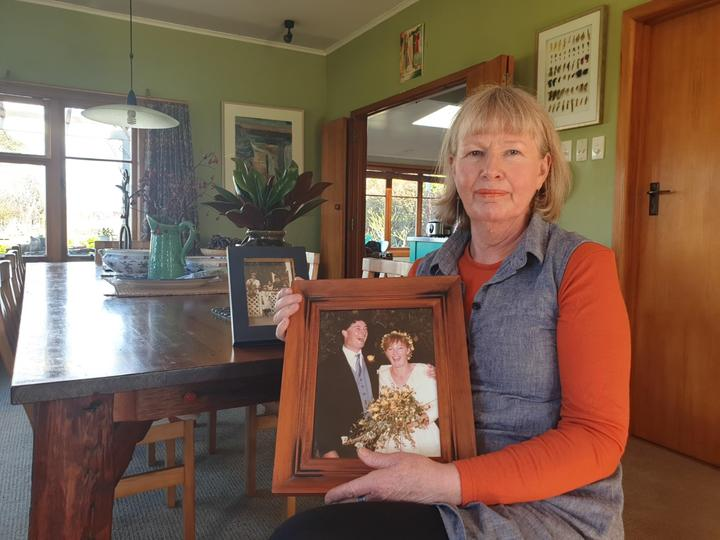 Heather Gregory, with a wedding photo showing her late husband Richard.