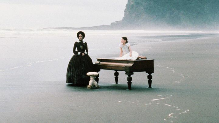 Screen shot from The Piano (with actors and piano on the beach)