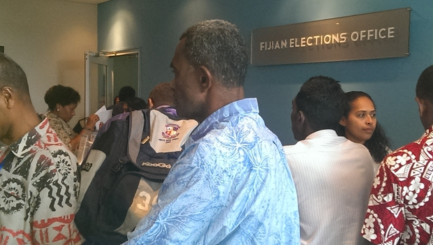 Crowd of polling workers at elections office after pages of names of people needed to work published in morning paper