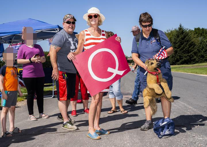MANKATO, MN - AUGUST 17: Kim Harty (C) holds a Q Anon sign outside Mankato Regional Airport.