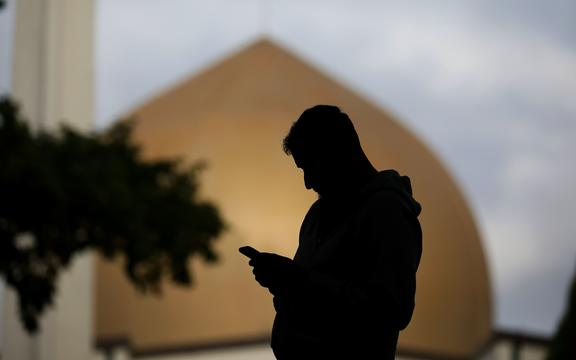 A member of the Muslim community uses his mobile phone out side the Al Noor mosque in Christchurch, New Zealand on March 15, 2020.