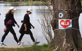 People wearing face masks exercise around the Albert Park Lake in Melbourne on August 26, 2020, as the city battles an outbreak of the COVID-19 coronavirus.