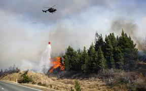 A helicopter drops water on a fire near lake Pukaki. 31 August 2020