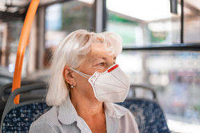 Caucasian woman in a protective mask sits in public transport at a distance of 2 m from other passengers. Protection and prevention covid 19, Coronavirus