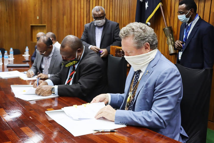Seated: Papua New Guinea's State Enterprises Minister, Sasindran Muthuvel (left), Prime Minister James Marape (centre) and the chairman of Fortescue Metals Group of Australia, Andrew Forrest, sign an agreement, Port Moresby, 1st September 2020.