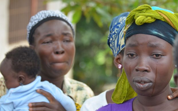 A woman cries after the death of her husband from Ebola.