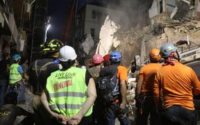 Lebanese and Chilean rescue workers watch as a crane lifts pieces of cement from a badly damaged building in Lebanon's capital Beirut, in search of possible survivors
