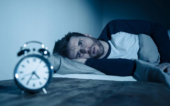 Insomnia Stress and Sleeping disorder concept. Sleepless desperate young caucasian man awake at night not able to sleep, feeling frustrated