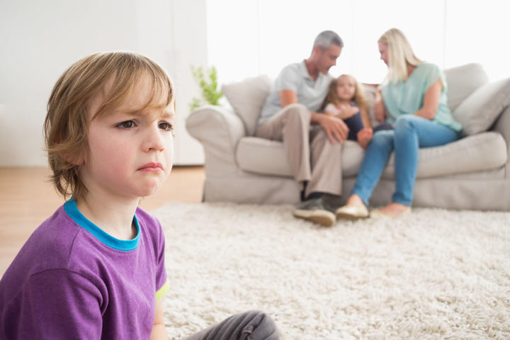 Photo of an upset boy sitting on floor while parents enjoying with sister on sofa at home