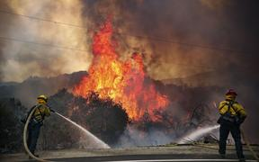 San Miguel County Firefighters battle a brush fire along Japatul Road during the Valley Fire in Jamul, California on September 6, 2020