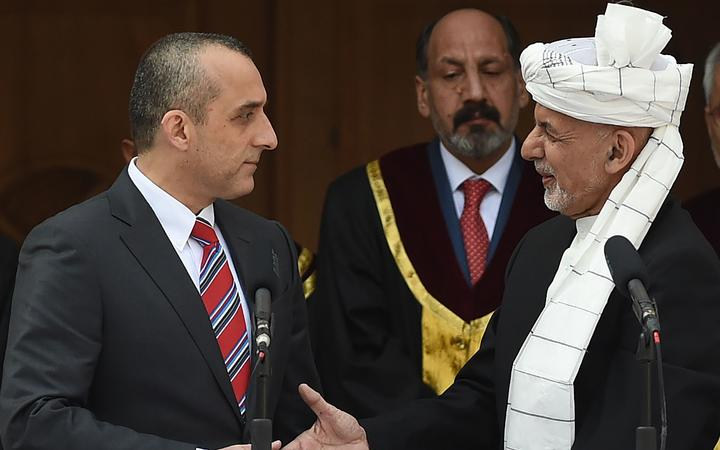Afghan President Ashraf Ghani (C) shakes hands with his first vice-president Amrullah Saleh (L)  during his swearing-in at the inauguration ceremony as the country's leader