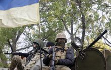 Ukrainian servicemen sit atop of an armored personnel carrier as they patrol in Donetsk region.