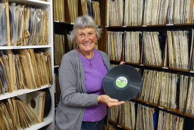Village Radio librarian Cherry Feasey with New Zealand's first record, Blue Smoke