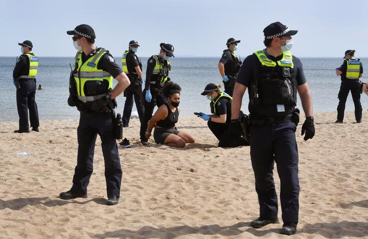 Police surround a protester at an anti-lockdown protest as they detain her at Elwood Beach in Melbourne in the weekend.