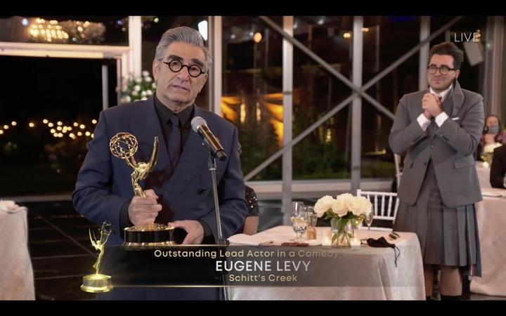 Canadian actor Eugene Levy speaks after receiving his Emmy while his son actor/director/writer Daniel Levy watches during the 72nd Primetime Emmy Awards ceremony held virtually on September 20, 2020.