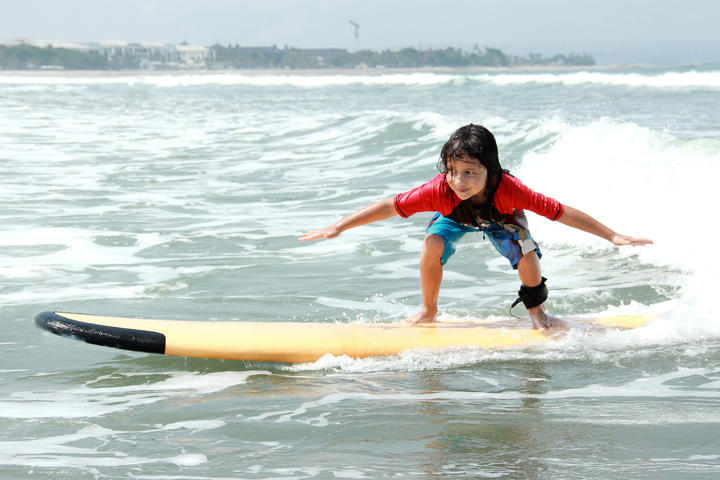 portrait of little boy learn to surf at ocean