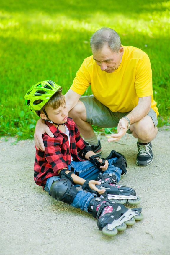 A photo of a father comforting his son who has fallen at skating on the roller skates.