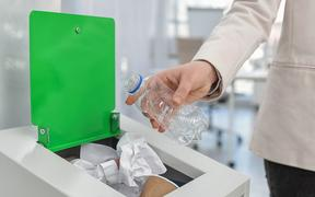 Woman putting used plastic bottle into trash bin in modern office, closeup. Waste recycling