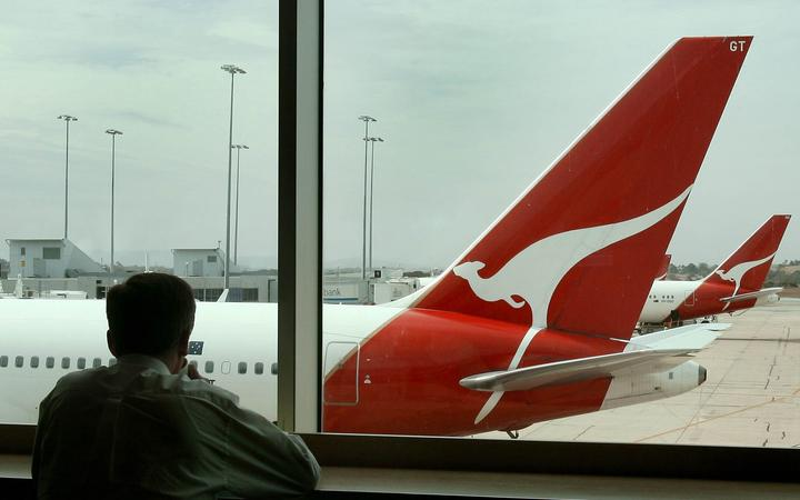 A man looks out over a line of Qantas planes at Melbourne's Tullamarine Airport as the Australian flag carrier and national icon Qantas accepted an increased 11.1-billion-dollar (8.7 billion USD) offer, 14 December 2006, from a private equity group, a day after rejecting a lower bid.