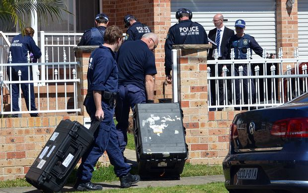Forensic experts collect evidence from a house in Sydney a part of  Australia's largest ever counter-terrorism raid.