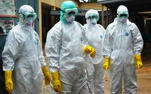 Health workers wearing protective suits prepare to carry the body of a victim of Ebola in Conakry, Guinea.