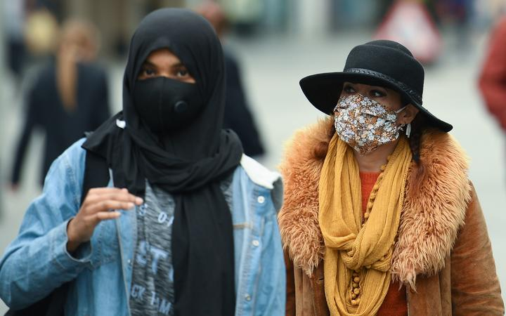 Women wear face masks or coverings due to the COVID-19 pandemic, as they walk in Liverpool, north west England on October 2, 2020, following the announcement of new local restrictions for certain areas in the northwest of the country, due to a resurgence of novel coronavirus cases.