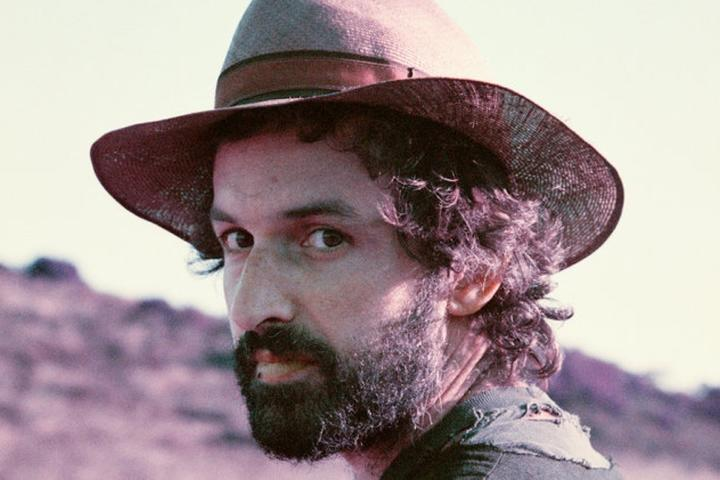 Joachim Cooder poses in the desert wearing a hat