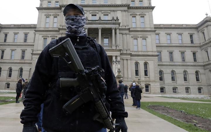 (FILES) In this file photo taken on April 15, 2020, an armed protester stands outside the Michigan State Capitol in Lansing, Michigan, during a demonstration against Michigan Governor Gretchen Whitmer's expanded the state's stay-at-home order to contain the spread of the coronavirus. -