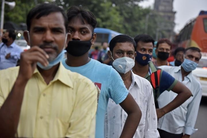 People stand on a line without maintaining social distancing amid coronavirus emergency in Kolkata, India,  on 8 October, 2020.