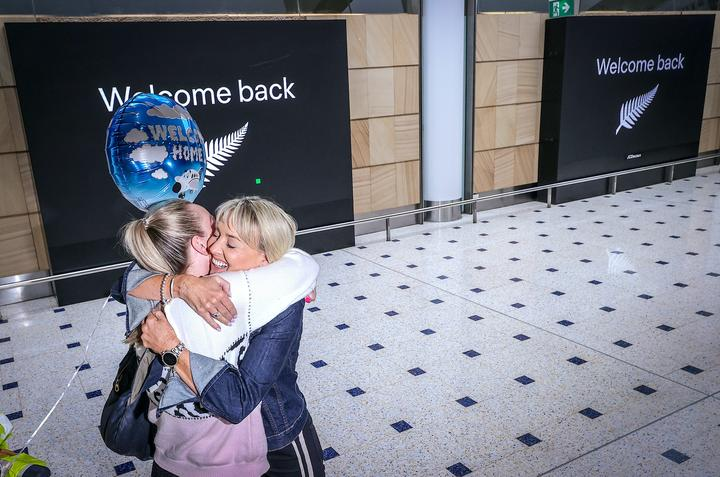 A passenger hugs a family member on arrival from New Zealand at Sydney International Airport on October 16, 2020, after Australia's border rules were relaxed under a new one-way trans-Tasman travel agreement that allow travellers from New Zealand to visit NSW without having to quarantine.