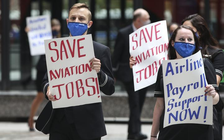 Airline industry workers hold signs during a protest in Federal Plaza in Chicago, Illinois, on September 9, 2020. - Other protests where held in