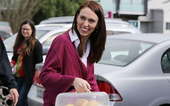 Labour Leader Jacinda Ardern arrives with scones as she visits Labour Election Day volunteers as polling booths open on election day for the  2020 General Election of New Zealand in Auckland on October 17, 2020. -