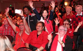 Labour party supporters react as they await Labour Leader Jacinda Ardern to arrive as they watch the results come for New Zealand's general election in Auckland on October 16, 2020.