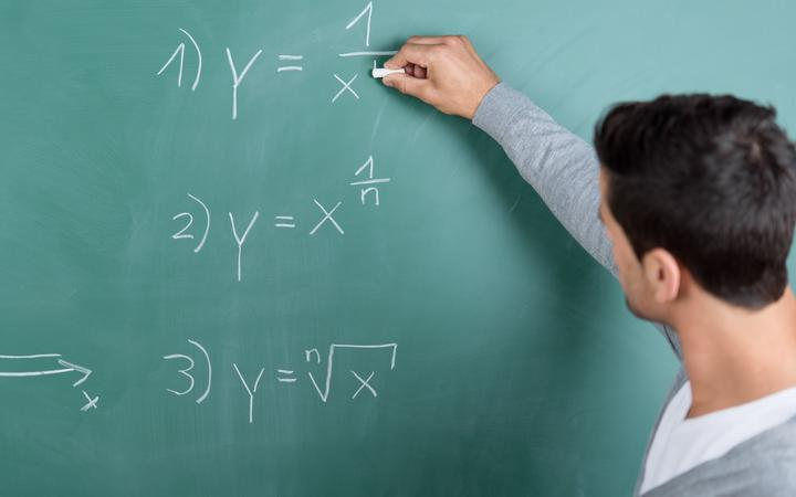 21205086 - male teacher with his back to the camera writing a mathematical formula on the blackboard in a classroom while teaching a class