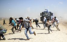 Kurdish protestors clash with Turkish soldiers near the Syrian border after it was temporarily closed by Turkish authorities