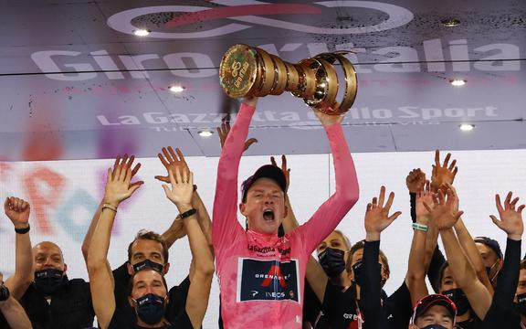 "Overall race winner Team Ineos rider Great Britain's Tao Geoghegan Hart wearing the leader's pink jersey holds the ""Never ending trophy"" (Trofeo Senza Fine) as he celebrates on podium after the the 21st and final stage of the Giro d'Italia 2020 cycling race."