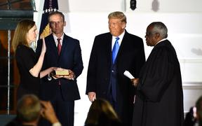 US President Donald Trump watches as Supreme Court Associate Justice Clarence Thomas (R) swears in Judge Amy Coney Barrett as a US Supreme Court Associate Justice, flanked by her husband Jesse M. Barrett, during a ceremony on the South Lawn of the White House October 26, 2020.