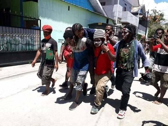 West Papuan students carry a wounded fellow demonstrator after security forces came to disband their rally, Waena, 27 October, 2020