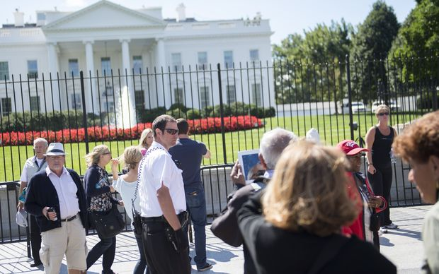 A member of the Secret Service's  uniformed division patrols outside the White House.