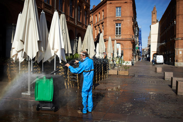 A worker cleans a bin in front of a closed cafe in Toulouse, on the second day of France's new lockdown.