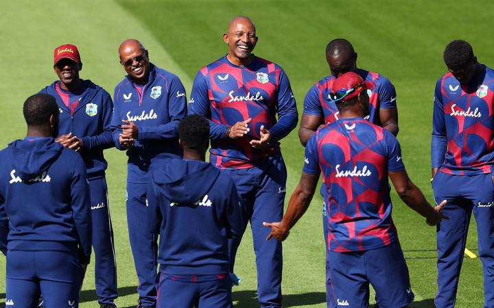 West Indies' head coach Phil Simmons (C) talks to his player ahead of the warm up before the start of play on the fourth day of the second Test cricket match against England at Old Trafford in Manchester on July 19, 2020.