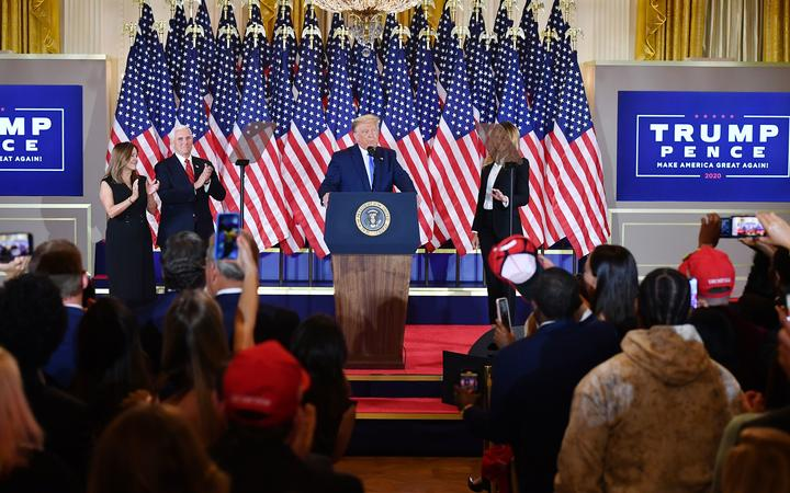 US President Donald Trump, flanked by Karen Pence (L), US Vice President Mike Pence (2nd L) and US First Lady Melania Trump (R), speaks during election night in the East Room of the White House in Washington, DC, early on November 4, 2020.