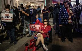 Supporters of US President Donald Trump hold signs and chant slogans during a protest outside the Philadelphia Convention center as votes continue to be counted following the 2020 US presidential election.