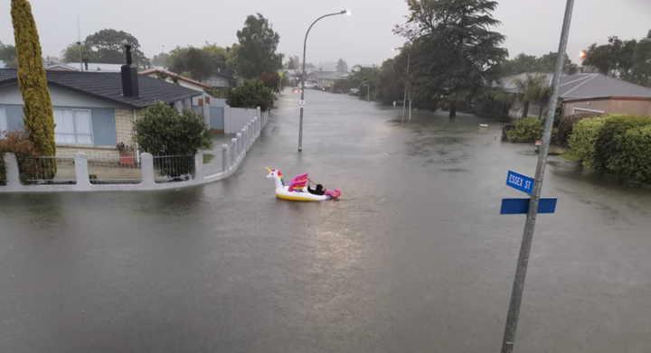 A man paddles an inflatable unicorn up the road, on Essex Street, Napier.