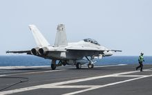 A United States F/A-18F Super Hornet lands on aircraft carrier USS George H.W. Bush after carrying out strikes on IS targets.